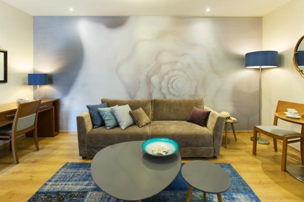 חדר אורחים משופץ: הים נכנס בעדינות לעיצוב באמצעות שימוש בצבע כחול ואלמנט הצדפה.